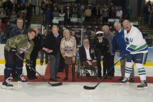 ET2016-0076-01 The Honourable Judith Guichon, Lieutenant Governor of British Columbia, prepares to drop the ceremonial puck at a game between the Vancouver Canucks Alumni and members of the Canadian Armed Forces (CAF) at the Q Centre, Colwood, British Columbia on 6 March, 2016. Standing from the left: Rear Admiral (RAdm) Gilles Couturier, Commander of Maritime Forces Pacific/ Joint Task Force (Pacific) and Captain of the Heroes Hockey Challenge (HHC) Warriors (CAF Members); Jane and Richard Nuttal; Paul Franklin; Leading Seaman (LS) Stephon Mullet; Former Vancouver Canucks Captain Orland Kurtenbach; and Alumni Captain Dave Babych. Image by LS Ogle Henry, MARPAC Imaging Services