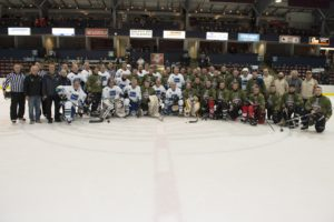 ET2016-0076-03 Members of the Heroes Hockey Challenge Team (Canadian Armed Forces Members), the Vancouver Canucks Alumni team and officials pose at centre ice at the conclusion of the game held at the Q Centre, Colwood, British Columbia on 6 March 2016. Image by LS Ogle Henry, MARPAC Imaging Services